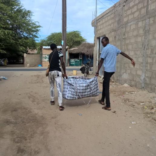 Diese grosse, schwere Tasche enthält Kleider und Spielzeuge für die Talibé-Kinder. Youssouf und Adama, die Brüder von Cheikh, tragen die schwere Tasche von Zuhause ins Center. Die Tasche wiegt bestimmt über 30 Kilos.