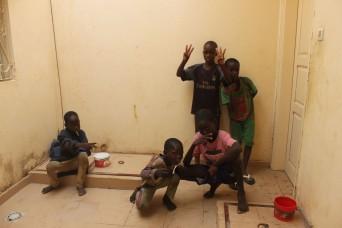 Bevor die Jungs, ihre Kleider bekommen haben, duschten sie sich alle. Diese Jungs stehen im kleinen Innenhof an, Die Dusche befindet sich hinter der geschlossenen Türe.