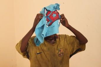 Ein anderer junge, der gerade sein neues T-Shirt bekommt und es sofort anzieht.