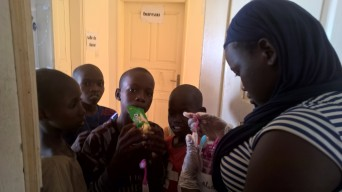 Alle Zahnbürsten sind mit dem Namen des Kindes angeschrieben und Awa verteilt sie, weil nicht alle ihre Namen lesen können.