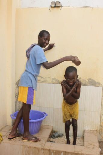 """Und dieser kleine Junge nimmt eine senegalesische Dusche im anderen Innenhof am """"Brunnen"""". Der grosse Junge ist Moussa. Er ist ein bisschen älter und hilft sehr gerne dem Team."""