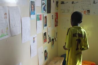 """Dieses Foto hat mich unter anderem zu meiner """"Ausmal-Aktion"""" inspiriert. Der Talibié-Junge steht vor den Bildern von den Kinder vom Schulhaus Mariazell in Sursee. Ich bin oft dort gestanden und habe den Kids die Namen der Jungs und Girls aus Sursee abgelesen. Sie schauen sehr gerne Bilder an. Also habe ich gedacht, dass ich eine ähnliche Aktion aber mit den Köpfen der Talibé-Jungs machen will."""