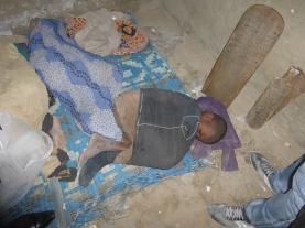 Ein älteres Fotos eines Talibé-Kindes. Mit einem Teppich, aber ohne Mückennetz