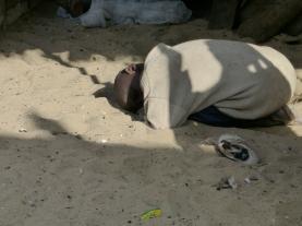 ein Talibé-Kind schläft am auf dem sandigen Boden